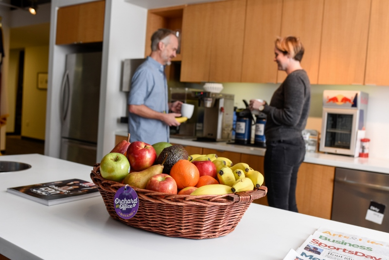Man and woman in office kitchen with fruit basket
