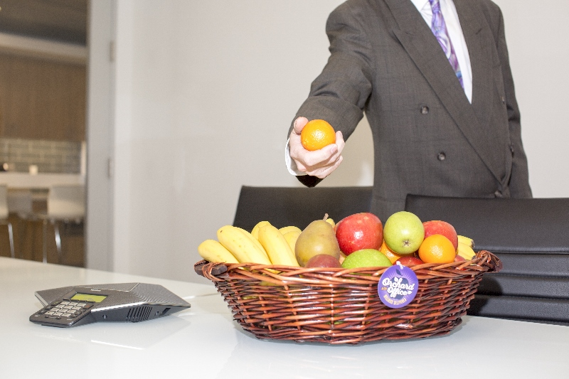 Suited man taking a fruit basket from a conference table