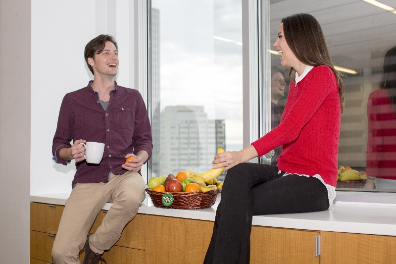 Two people laughing by a basket of fruit