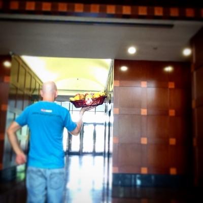 Man delivering fruit basket in office building