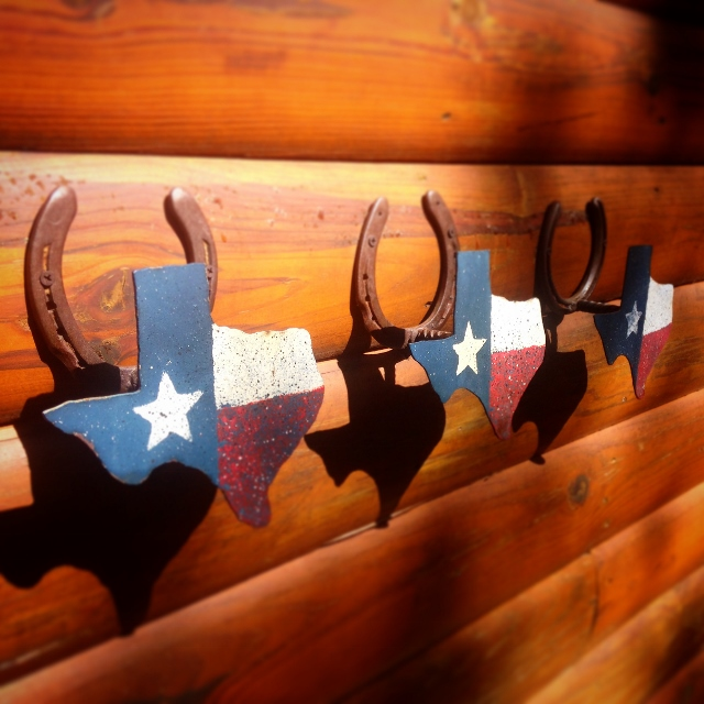 Horseshoe and Texas-shaped towel racks on a wooden wall