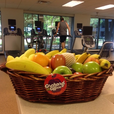A fresh fruit basket in a fitness center while a man uses a treadmill