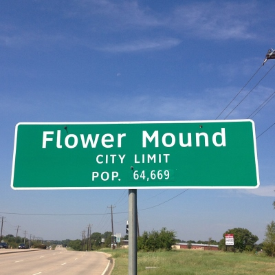Street sign for Flower Mound city limits with half moon in background