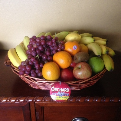 Two wicker baskets display a variety of fresh fruit