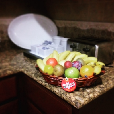 A fruit basket displayed near a toaster and breakfast condiments