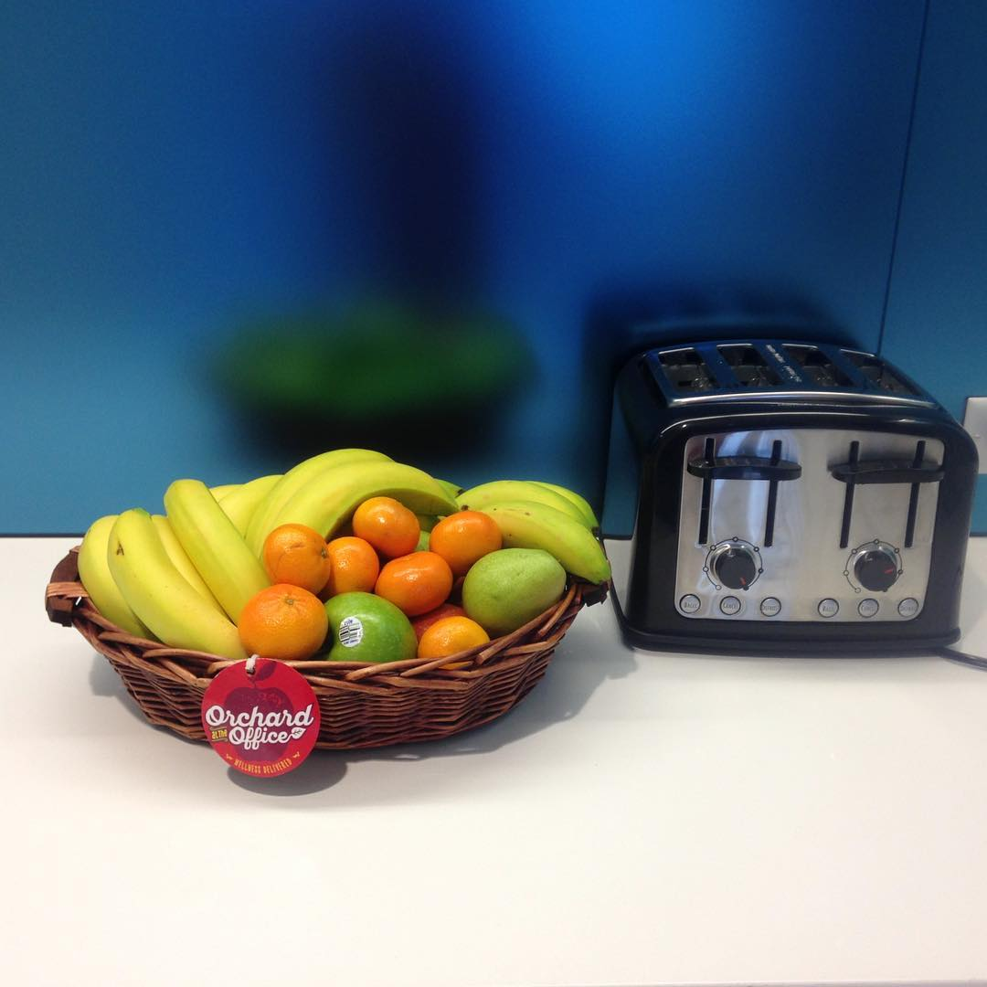 Fruit basket seated next to toaster in front of blue backsplash