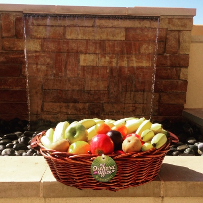 Basket of fruit in front of outdoor rock garden with waterfall