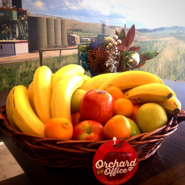 Fresh fruit basket in front of a mural depicting an agricultural scene
