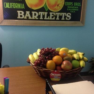 Wicker fruit basket seated atop wooden office desk