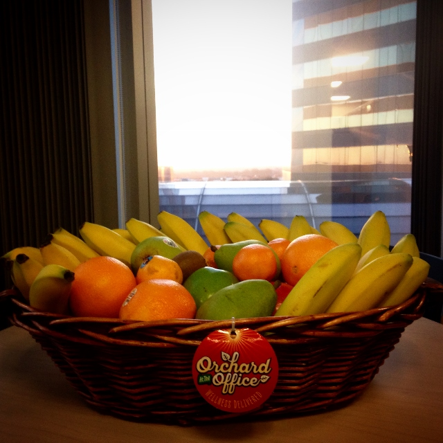 A fruit basket sits on a table in front of a high-rise window during sunrise