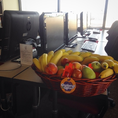 Basket of fresh fruit in an educational setting next to computer terminals