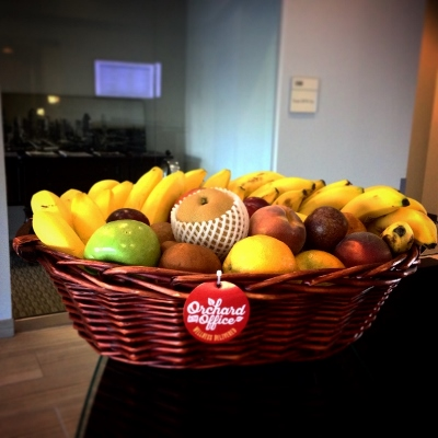 A fresh fruit basket appears in the foreground with an office entrance behind