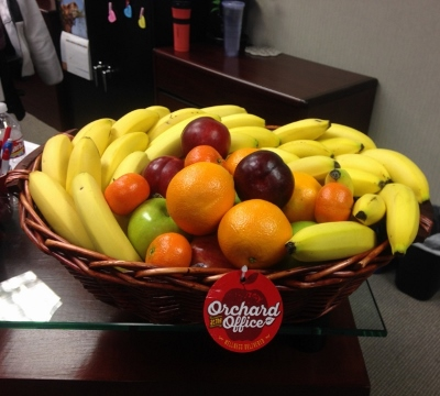 Large basket of bananas, apples, and other fruit at a reception desk