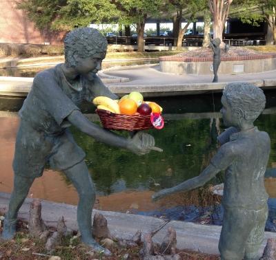 Wicker fruit basket placed amusingly on bronze statues