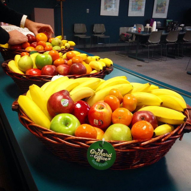 Three large fresh fruit baskets in corporate kitchen