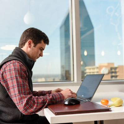 Man working on laptop with fruit