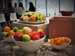 Fresh fruit displayed in white ceramic bowls in office kitchen