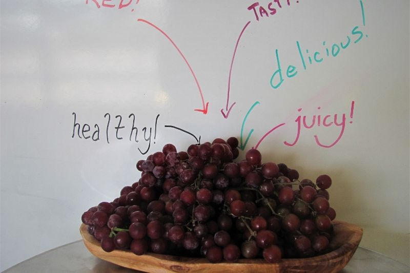 Red grapes in front of a whiteboard