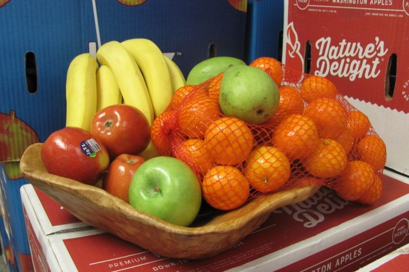 A wooden tray containing fresh fruit