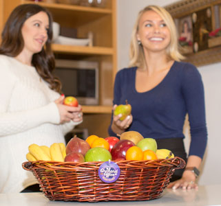 Happy office employees with fresh fruit